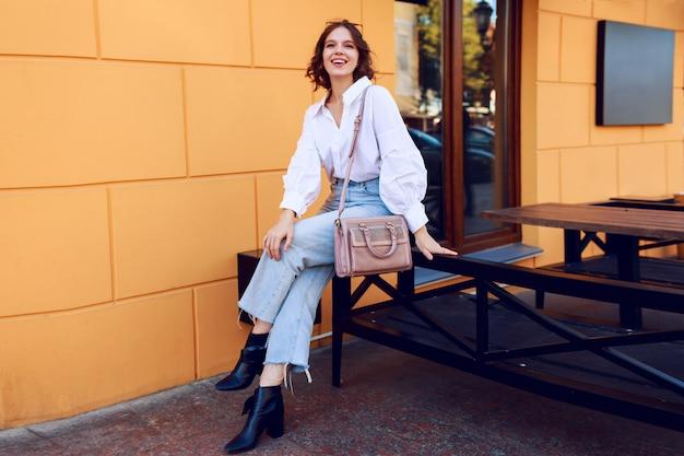 Imagen de moda de niña bonita morena con peinado corto en elegante blusa blanca casual y jeans. botas de cuero negro con tacones. chica sentada cerca de café moderno con paredes amarillas.