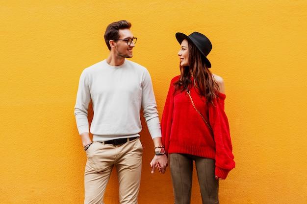 Imagen de moda otoño de elegante elegante pareja de enamorados cogidos de la mano y mirando el uno al otro con placer.