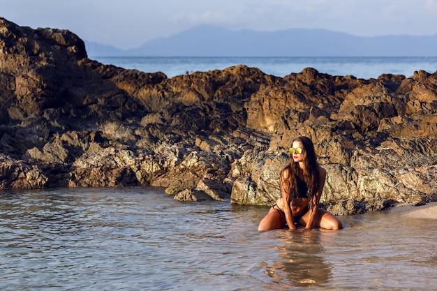 Imagen de moda tropical paraíso de mujer sexy posando en la playa solitaria, increíble atmósfera de frío, tomando el sol, hermosa naturaleza alrededor.