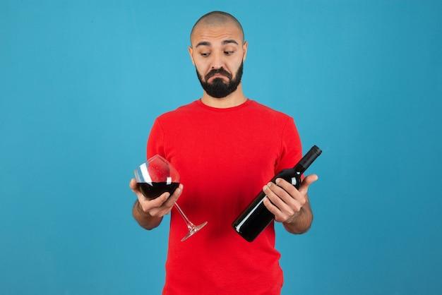 Imagen de un modelo de hombre joven en t-short rojo sosteniendo una botella de vino con vidrio.