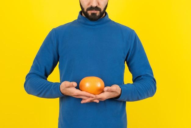 Imagen de un modelo de hombre sosteniendo una fruta naranja contra la pared amarilla.