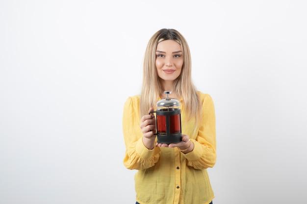 Imagen de un modelo de mujer bonita joven sosteniendo una tetera.