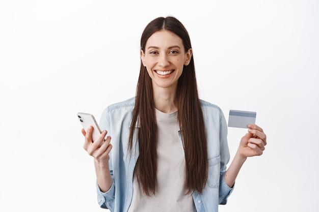 Imagen de modelo de mujer joven con tarjeta de crédito y teléfono inteligente, concepto de compras en línea, pago sin contacto y entrega por internet, de pie sobre una pared blanca