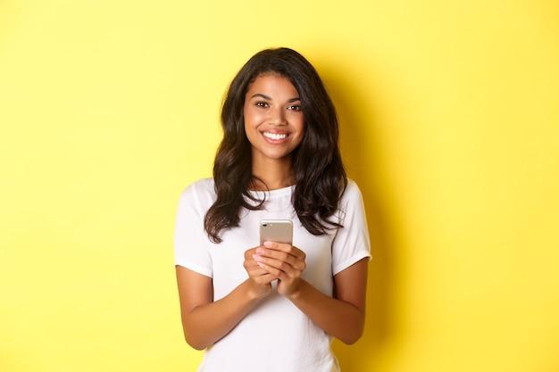 Imagen de la moderna niña afroamericana sonriendo con teléfono móvil de pie sobre fondo amarillo
