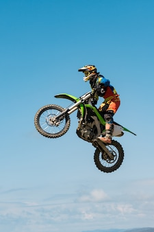 Una imagen de un motociclista haciendo un truco y saltando en el aire