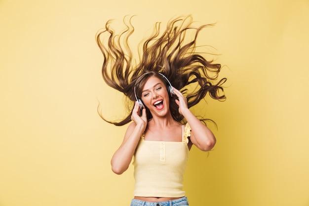 Imagen de mujer alegre de 20 años cantando y disfrutando de la melodía con agitación del cabello mientras escucha música a través de auriculares, aislado sobre fondo amarillo