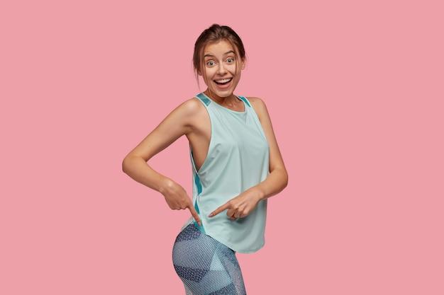Imagen de mujer alegre apunta a las nalgas