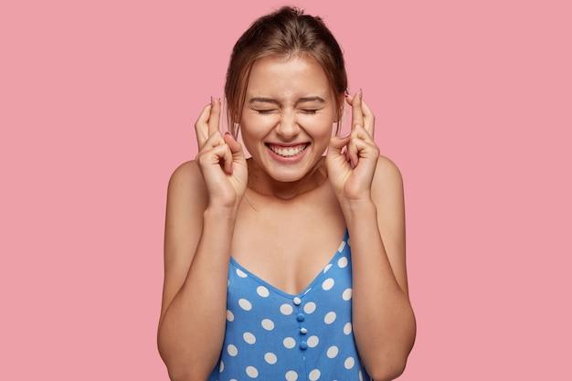 Imagen de mujer alegre complacida cruza los dedos