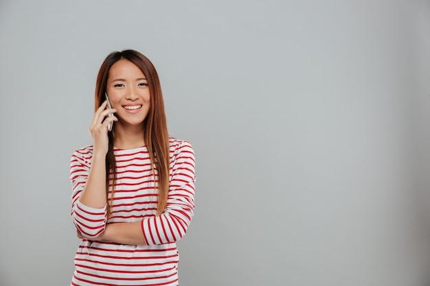 Imagen de la mujer asiática joven feliz que habla por la situación del teléfono aislada sobre la pared gris. mirando la cámara.