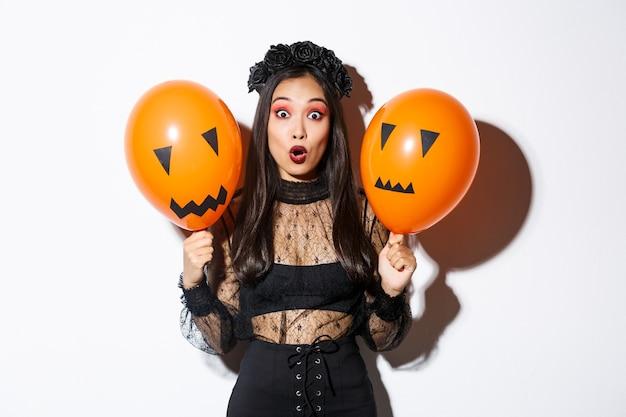 Imagen de mujer asiática sorprendida en traje de bruja celebrando halloween, sosteniendo globos con caras aterradoras