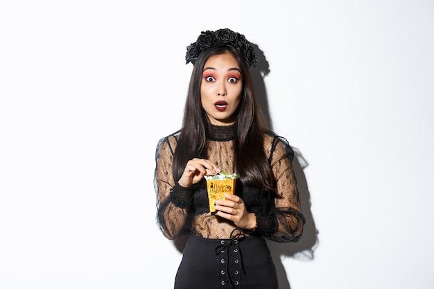 Imagen de mujer asiática sorprendida en traje de halloween de bruja mirando a la cámara mientras sostiene dulces en la bolsa de truco o trato, de pie sobre fondo blanco.