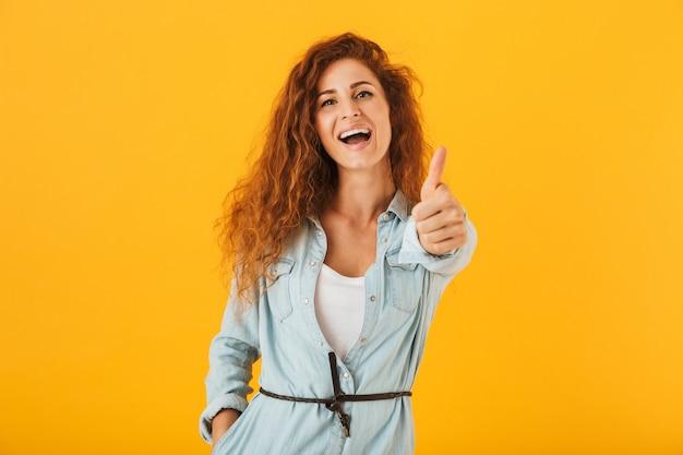 Imagen de mujer atractiva feliz sonriendo y mostrando el pulgar hacia arriba, aislado sobre fondo amarillo