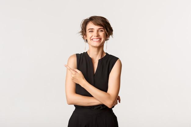 Imagen de una mujer bonita alegre riendo y señalando con el dedo la esquina superior izquierda, mostrando el logo, blanco.