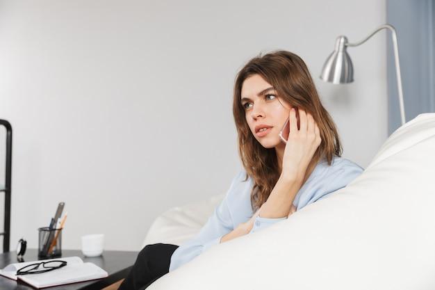 Imagen de una mujer bonita joven hermosa pensativa pensativa en casa adentro hablando por teléfono móvil.