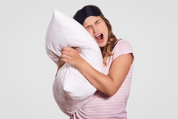 La imagen de una mujer bosteza, tiene expresión soñolienta, viste ropa doméstica, lleva una almohada blanca suave y posa en blanco. concepto de personas, descanso, confort, cansancio, sueño
