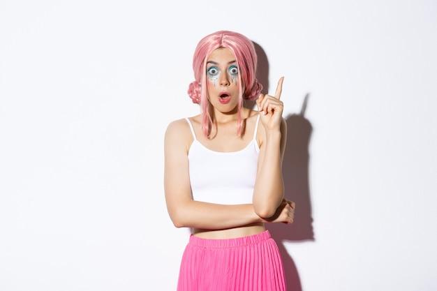Imagen de mujer creativa con peluca de fiesta rosa y maquillaje brillante, sugiriendo una idea, levantando el dedo índice en el signo de eureka, de pie sobre fondo blanco.