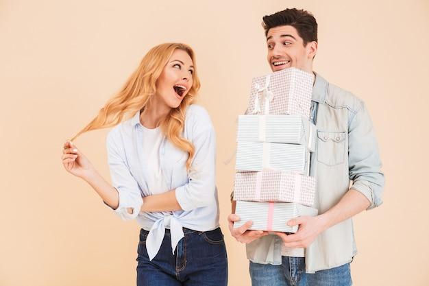 Imagen de una mujer encantadora regocijándose y expresando sorpresa mientras un hombre guapo sostiene un montón de cajas de regalo, aisladas sobre una pared beige