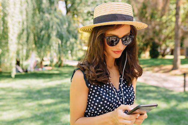 Imagen de mujer de estilo encantador está caminando en el parque de verano con sombrero de verano y gafas de sol negras y un lindo vestido.