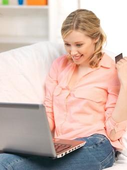 Imagen de mujer feliz con computadora portátil y tarjeta de crédito.