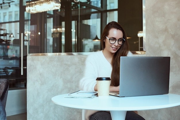 Imagen de la mujer feliz que usa la computadora portátil mientras que se sienta en el café. merican mujer sentada en una cafetería y trabajando en equipo portátil.