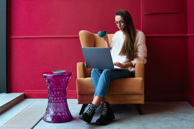 Imagen de la mujer feliz que usa la computadora portátil mientras que se sienta en el café.