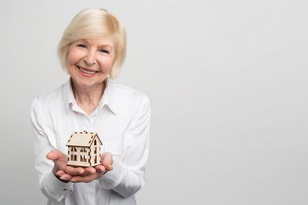 Una imagen de una mujer feliz y sonriente que tiene una pequeña casa de juguete en la mano. ella no es joven en este momento y quiere tener algunas garantías para el futuro.