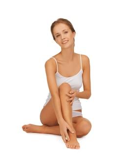 Imagen de mujer hermosa en ropa interior de algodón tocando sus piernas