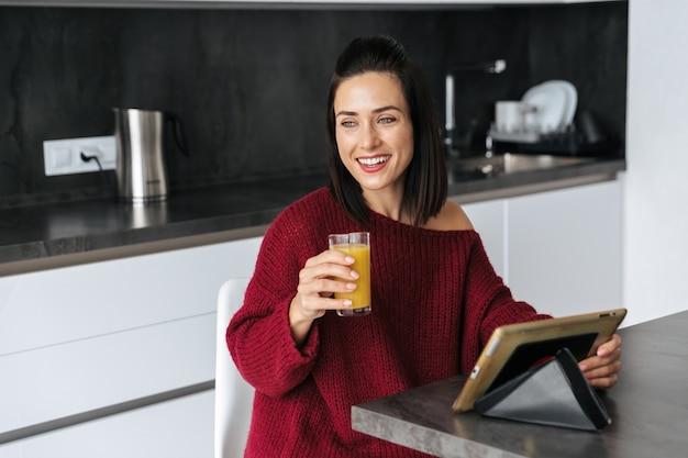 Imagen de una mujer increíble en el interior de su casa en la cocina con tablet pc bebiendo jugo.