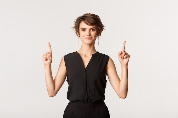 Imagen de mujer joven atractiva y elegante confiada que señala con el dedo hacia arriba, mostrando el logotipo, blanco.