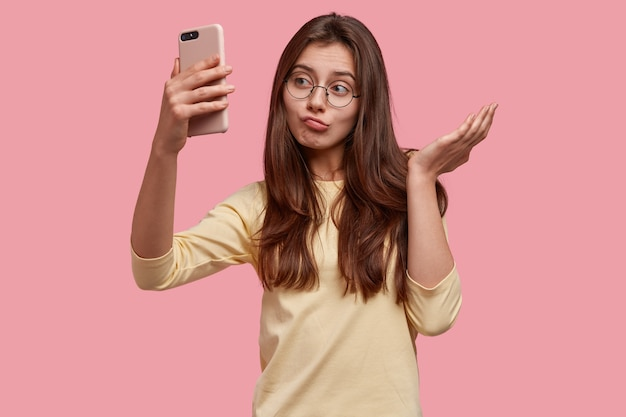Imagen de mujer joven caucásica bastante vacilante mira con apatía de teléfono inteligente, toma selfie o hace videollamada