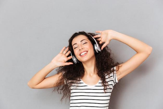 Imagen de una mujer joven complacida en camiseta a rayas que disfruta de sus canciones favoritas escuchando melodías a través de auriculares con los ojos cerrados sobre la pared gris