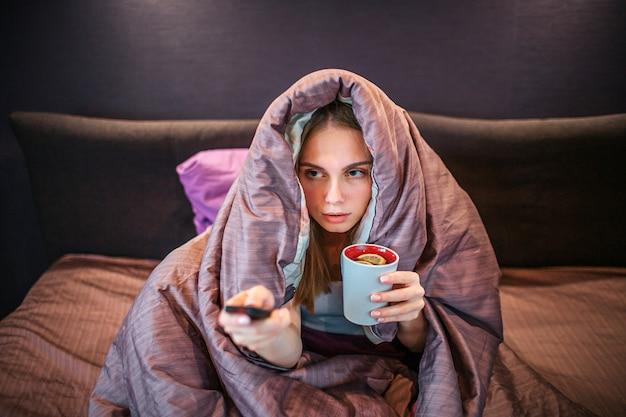 Imagen de mujer joven cubierta con una gruesa manta y ve la televisión. ella tiene el control remoto en una mano y una taza de té con un trozo de limón en la otra. la niña esta enferma.