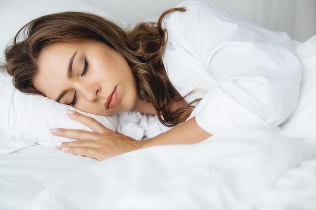 Imagen de mujer joven feliz vestida con una camisa blanca, acostada en una cama blanca en su casa en la habitación. mañana.