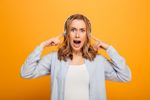 Imagen de una mujer morena con frenillos reacciona emocionalmente mientras escucha su canción favorita con auriculares inalámbricos, aislado sobre un espacio amarillo