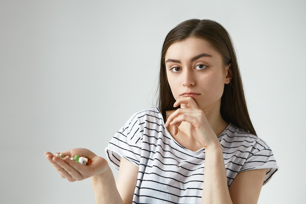 Imagen de mujer morena joven incierta sosteniendo la boca llena de pastillas de colores, con expresión de duda pensativa, tocando la barbilla, pensando en tomar medicamentos o no mientras sufre de resfriado