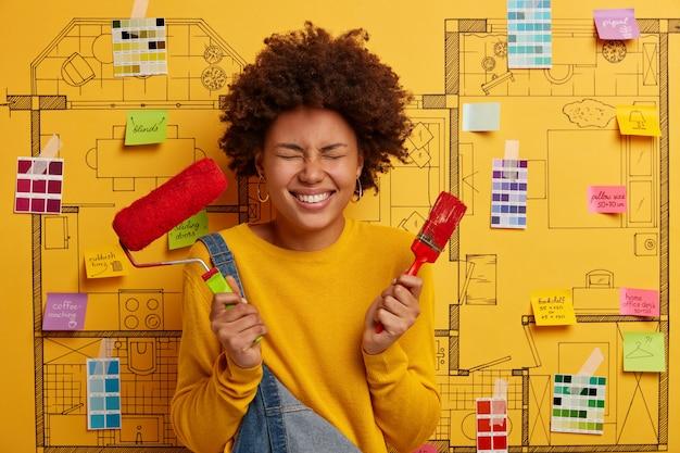 Imagen de mujer de pelo rizado alegre sostiene pincel y rodillo, restaura paredes en color rojo, vestida con ropa casual