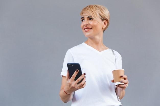 Imagen de mujer rubia alegre con ropa casual sonriendo mientras sostiene el café de la taza de papel y el teléfono inteligente, aislado sobre la pared gris