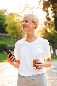 Imagen de mujer rubia alegre con ropa casual sonriendo mientras sostiene el teléfono inteligente y café para llevar, durante un paseo en el parque verde