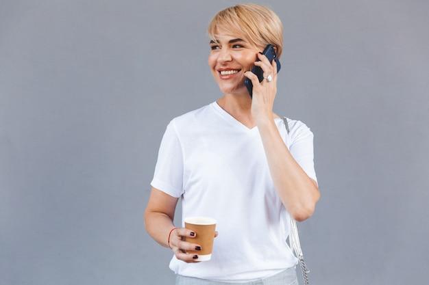 Imagen de mujer rubia satisfecha con camiseta blanca de pie aislado sobre una pared gris y sosteniendo café de una taza de papel mientras habla por teléfono celular
