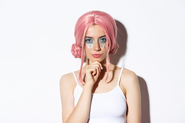 Imagen de mujer segura de sí misma en peluca rosa y disfraz de halloween, pensando, mirando a la cámara con interés, de pie sobre fondo blanco.