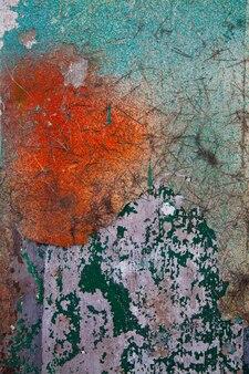 Imagen de muro de hormigón envejecido verde, blanco y rojo que se está pelando con antecedentes de edad