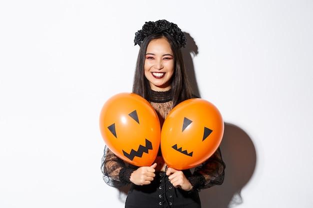 Imagen de niña asiática en traje de bruja malvada sosteniendo dos globos naranjas con caras aterradoras, celebrando halloween, de pie sobre fondo blanco.
