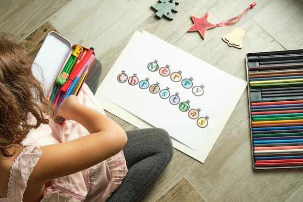 Imagen de niña coloreando letras de feliz navidad en un papel blanco con lápices de colores