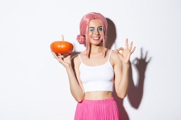 Imagen de niña feliz celebrando halloween, vistiendo peluca rosa, sosteniendo calabaza y mostrando el signo de bien, de pie sobre fondo blanco.