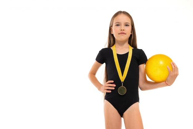 Imagen de una niña gimnasta en calcetines cortos blancos y trico negro de altura completa con pelota amarilla en sus manos y una medalla alrededor del cuello aislado en un blanco