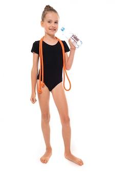Imagen de niña gimnasta en trico negro en toda su altura con una cuerda para saltar alrededor de su cuello y una botella de agua en la mano aislado en un blanco