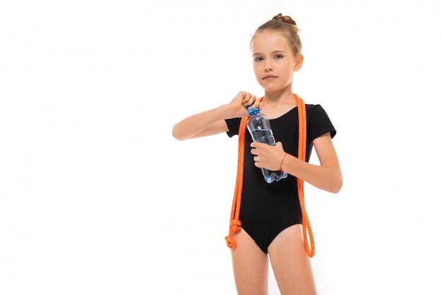Imagen de niña gimnasta en trico negro en toda su altura con una cuerda para saltar alrededor de su cuello y una botella de agua en la mano aislado sobre un fondo blanco.