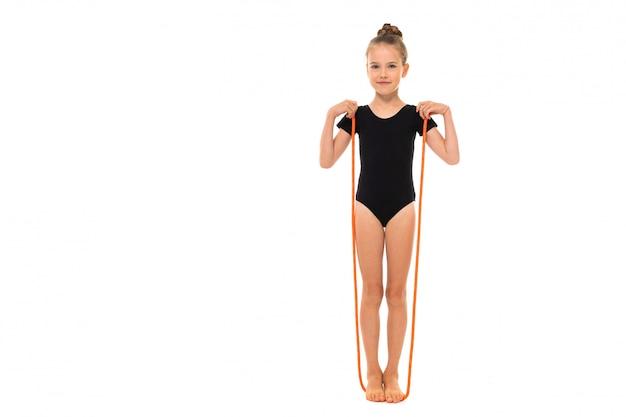 Imagen de niña gimnasta en trico negro en toda su altura se encuentra en una cuerda de saltar aislado sobre un fondo blanco.