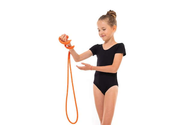 Imagen de niña gimnasta en trico negro en toda su altura mantener una cuerda de saltar en la mano aislada sobre un fondo blanco.