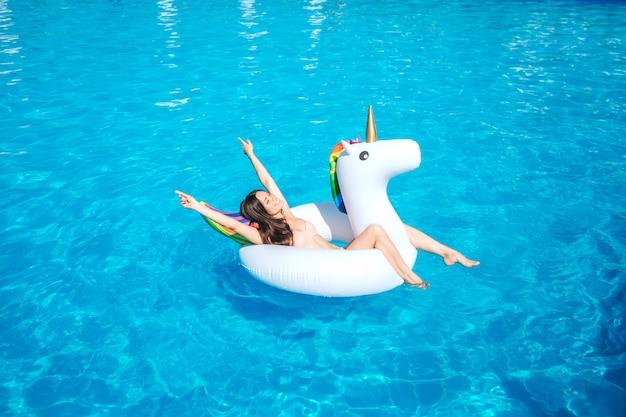 Una imagen de una niña nadando en la piscina sola. ella se acuesta sobre el colchón de aire y posa. chica os descansando. ella se divierte un poco.